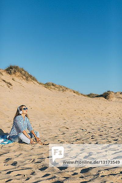 Portugal  Aveiro  Frau sitzt in der Nähe einer Stranddüne und hört Musik mit Kopfhörern