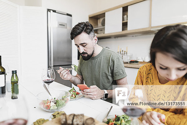 Man checking messages on mobile phone while having lunch with his girlfriend at home