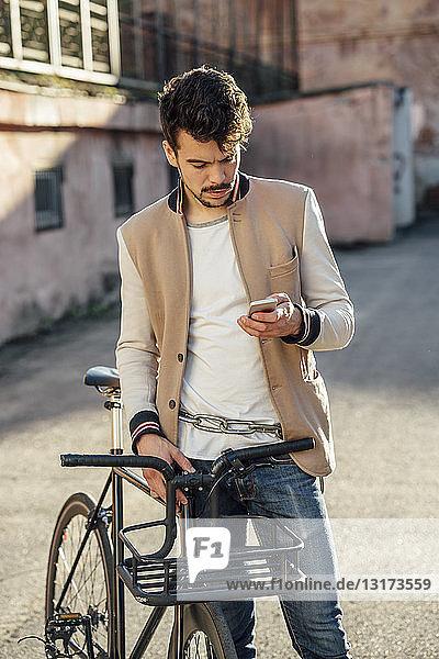 Junger Mann mit Pendler-Fixie-Fahrrad auf einem Hinterhof in der Stadt beim Handy-Check