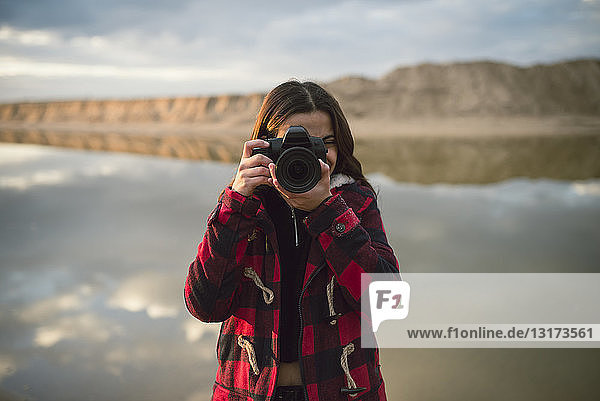 Young woman taking picture with camera on the beach