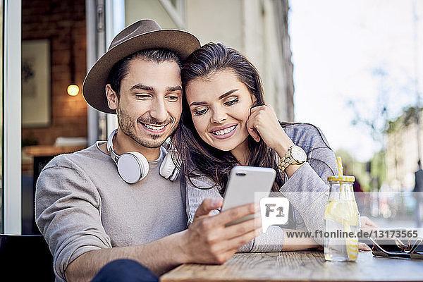 Glückliches junges Paar betrachtet Handy im Außencafé