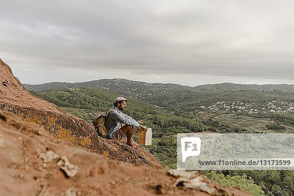 Junger Mann mit Rucksack  sitzt auf einem Berg und schaut auf die Aussicht