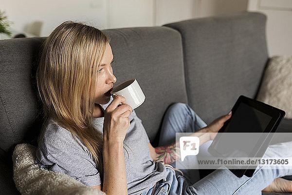 Junge Frau sitzt auf Couch  trinkt Kaffee und hält Tablette