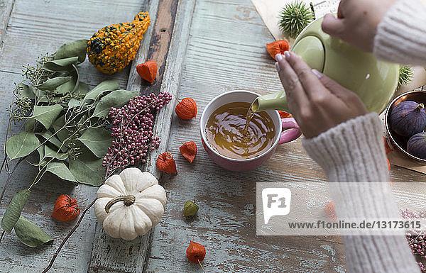 Frauenhände gießen Tee in eine Tasse