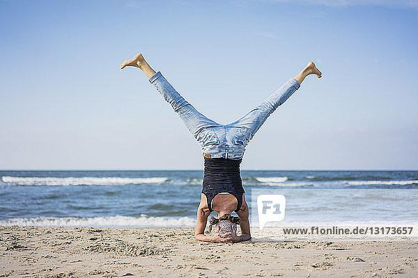 Eine reife Frau macht einen Kopfstand am Strand