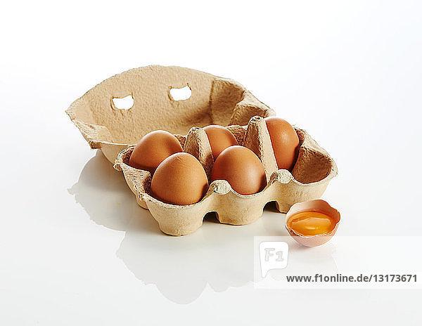 Eierschachtel mit braunen Eiern und einem geöffneten Ei auf weißem Hintergrund