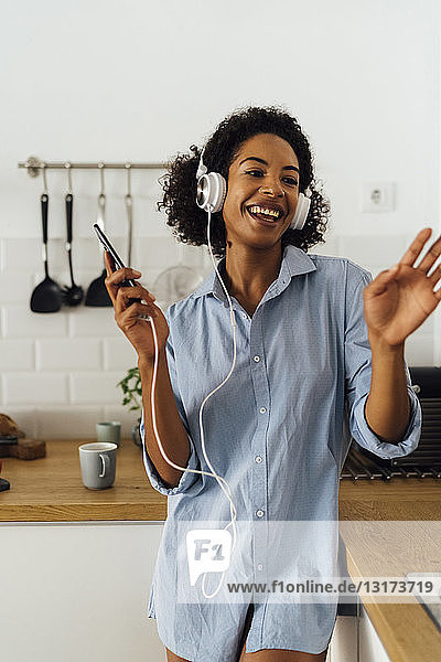 Woman dancing and listening music in the morning in her kitchen
