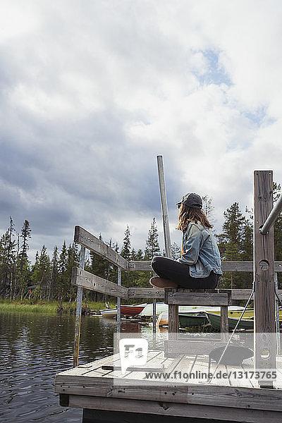 Finnland  Lappland  entspannte Frau sitzt auf einem Steg an einem See