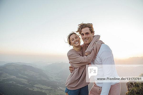Schweiz  Grosse Mythen  Porträt eines glücklichen jungen Paares  das sich bei Sonnenaufgang in einer Berglandschaft umarmt