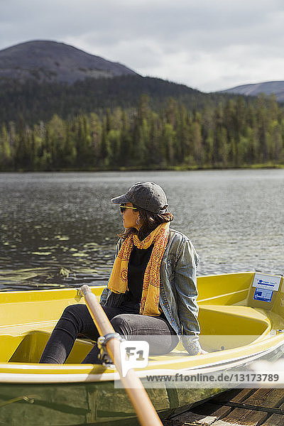 Finland  Lapland  woman sitting in a boat on a lake