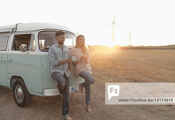 Glückliches junges Paar steht am Wohnmobil in ländlicher Landschaft bei Sonnenuntergang