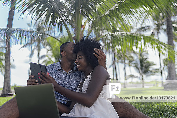 Young man kissing girlfriend with tablet on lawn in a park