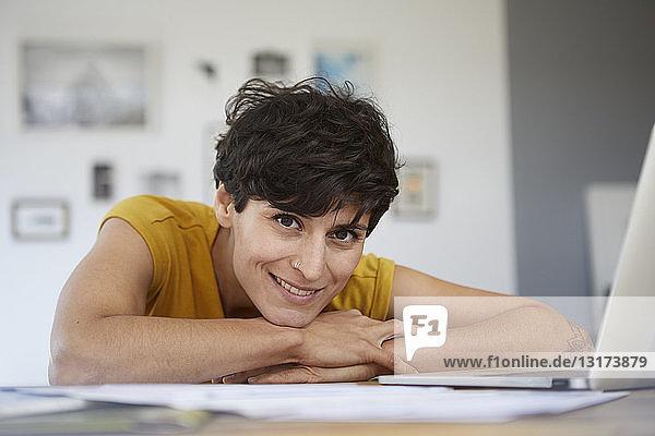 Porträt einer lächelnden Frau zu Hause  die sich auf den Tisch lehnt