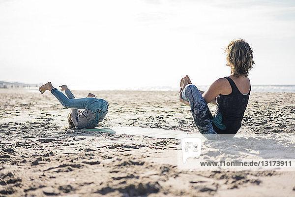 Mutter und Tochter praktizieren Yoga am Strand