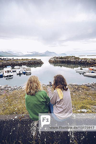 Norwegen  Senja  zwei junge Frauen sitzen mit einem Mobiltelefon an einem kleinen Hafen