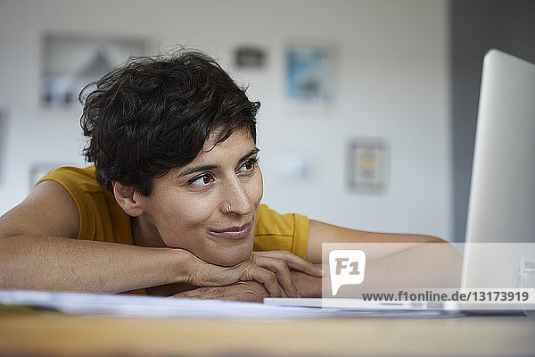 Smiling woman at home leaning on table looking at laptop