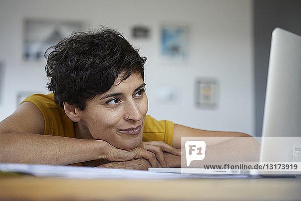Lächelnde Frau zu Hause lehnt am Tisch und schaut auf den Laptop