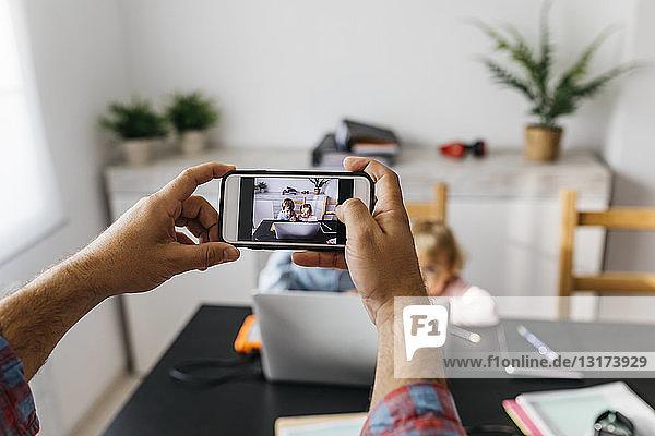 Vater macht Fotos von seinen Kindern mit seinem Laptop