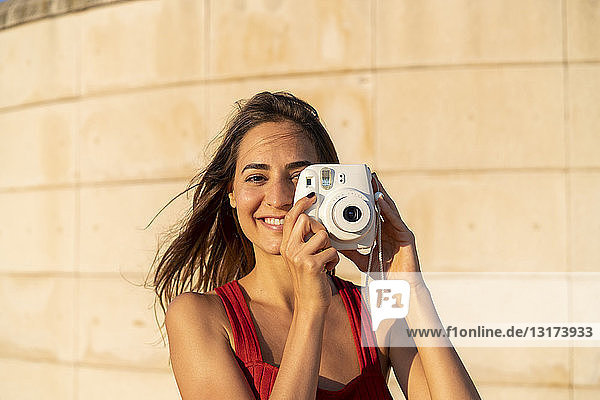 Portrait of smiling young woman taking instant photo outdoors