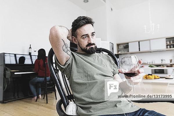Paar zu Hause  Mann trinkt Wein  Frau spielt im Hintergrund Klavier