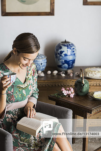Young woman drinking cup of tea while reading a book at home