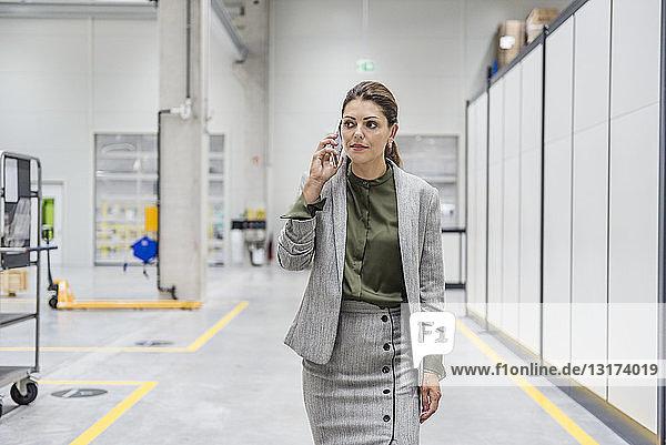 Geschäftsfrau geht in Fabrikhalle  spricht am Telefon