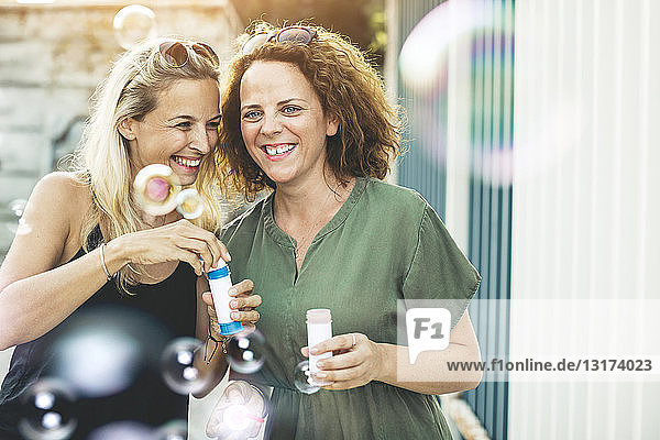 Two happy women with soap bubbles outdoors