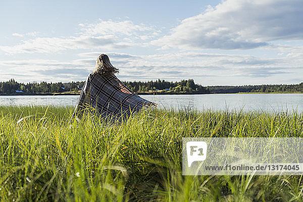 Finnland  Lappland  Frau in eine Decke gewickelt am Seeufer