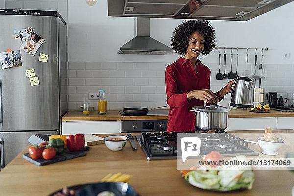 Frau  die in der Küche steht und Essen zubereitet