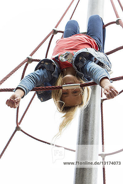 Blond girl hanging upside down on jungle gym at playground