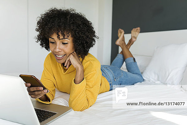 Smiling woman lying on bed using cell phone and laptop