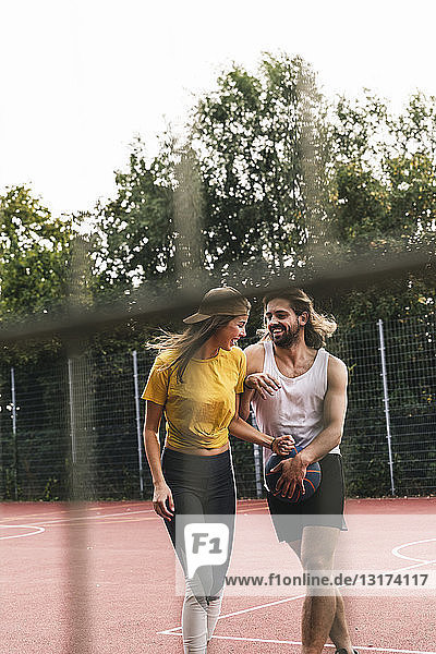 Young couple having fun on the basketball ground