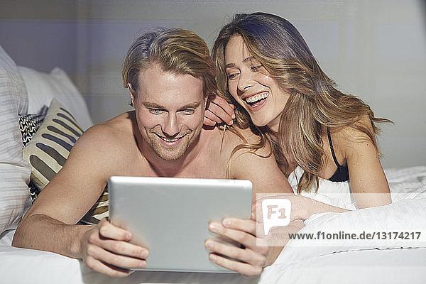 Porträt eines entspannten Paares mit auf dem Bett liegendem Tablett