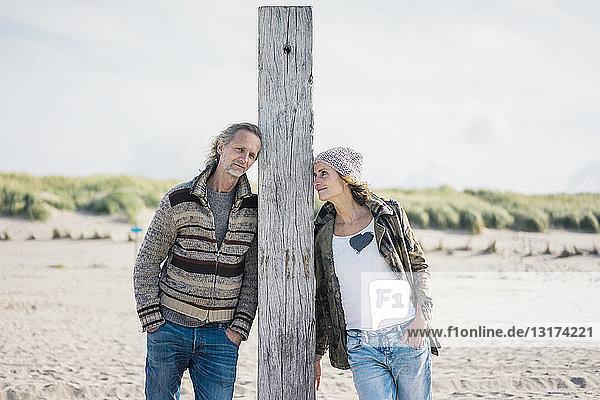 Erwachsenes Paar am Strand  auf Holzpfahl gelehnt