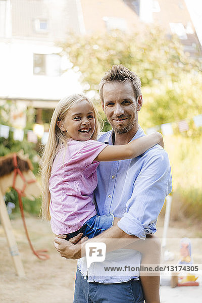 Portrait of smiling father carrying daughter in garden
