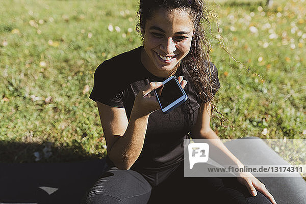 Happy sporty young woman having a break on a meadow using cell phone