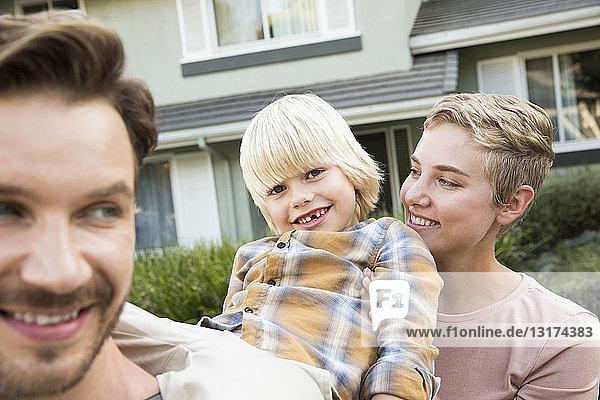 Porträt von glücklichen Eltern mit Sohn vor ihrem Haus