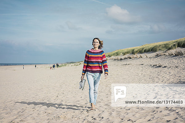 Reife Frau geht barfuss am Strand