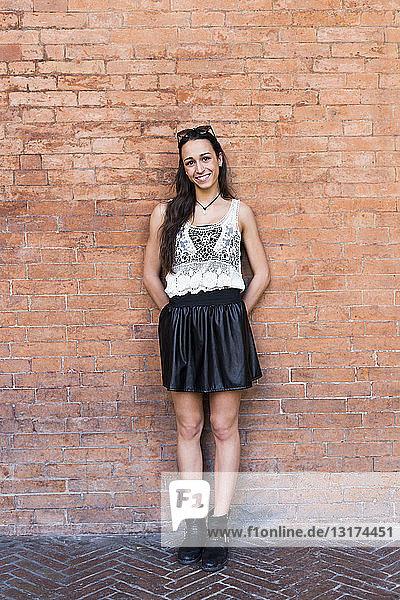 Porträt einer modischen jungen Frau vor einer Backsteinmauer stehend