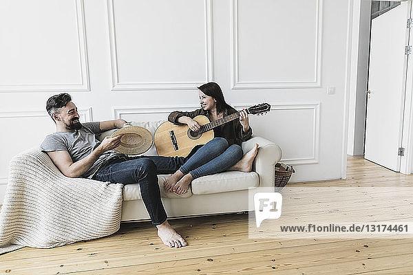 Entspanntes Paar sitzt auf Couch  Frau spielt zu Hause Gitarre