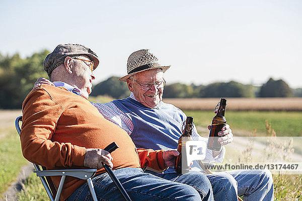 Zwei alte Freunde sitzen auf den Feldern  trinken Bier und reden über alte Zeiten