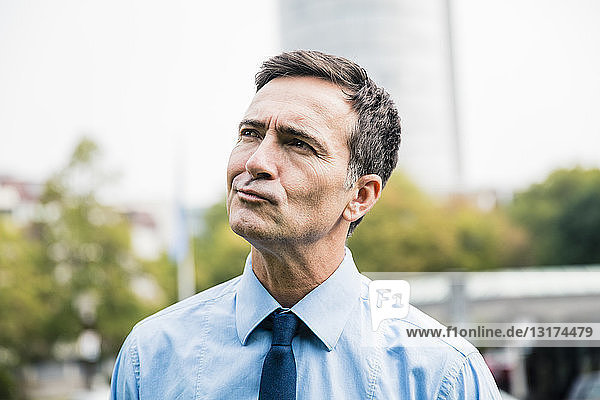 Portrait of businessman in city park thinking