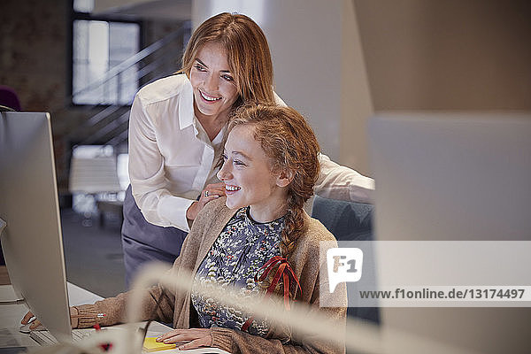 Colleague helping young woman at work