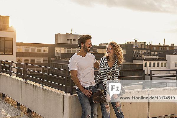 Glückliches junges Paar entspannt sich bei Sonnenuntergang auf der Dachterrasse