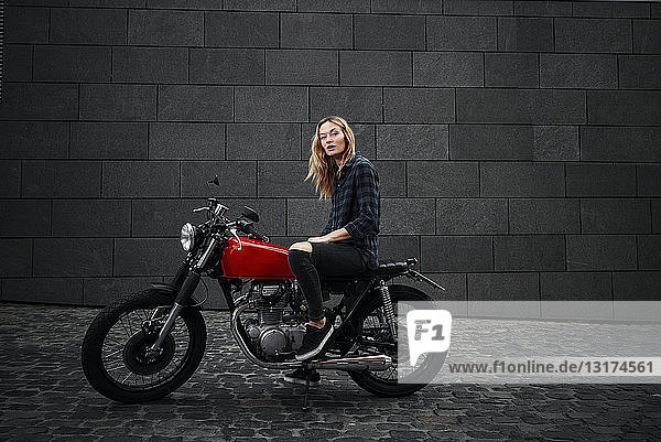 Porträt einer selbstbewussten jungen Frau auf Motorrad