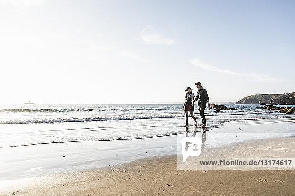 Frankreich,  Bretagne,  junges Paar geht Hand in Hand am Strand