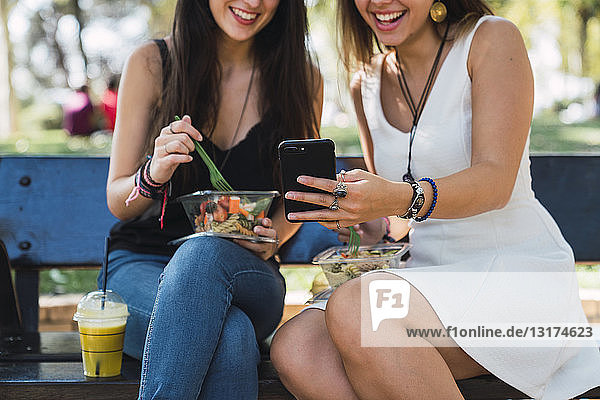 Girl friends sitting in a park  eating salad