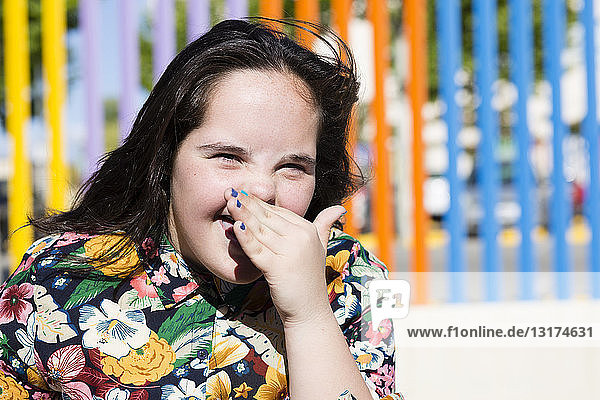 Teenager girl with down syndrome laughing  hand covering mouth
