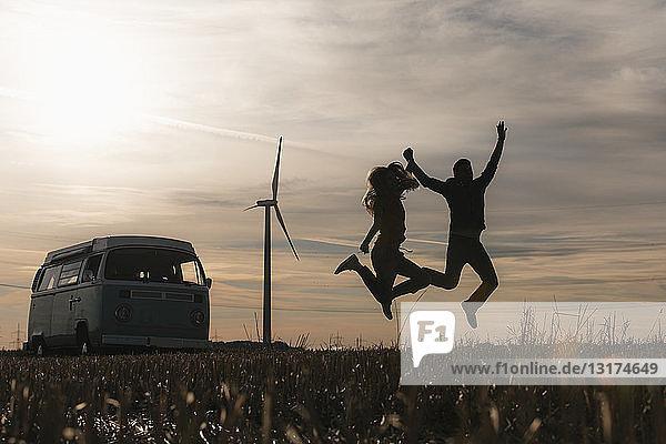 Überschwängliches Paar springt in der Abenddämmerung auf Wohnmobil in ländlicher Landschaft