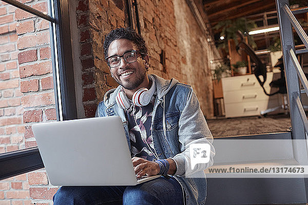 Young man with earphones sitting on office stairs  using laptop